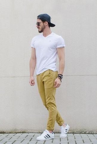 Comment porter: t-shirt à col en v blanc, pantalon chino moutarde, baskets basses en cuir blanches, casquette de base-ball noire