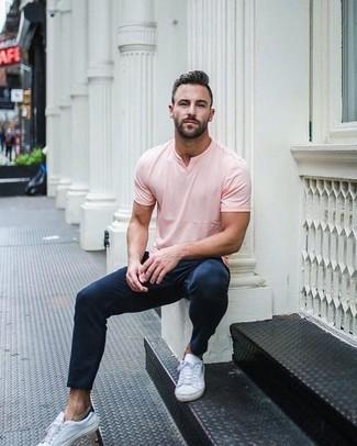 La polyvalence d'un t-shirt à col en v rose et d'un pantalon chino bleu marine en fait des pièces de valeur sûre. Cette tenue se complète parfaitement avec une paire de des baskets basses en cuir blanches.