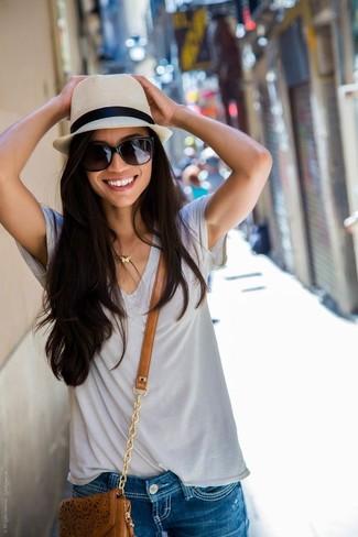 Comment porter: t-shirt à col en v gris, short en denim déchiré bleu, sac bandoulière en cuir marron, chapeau de paille beige