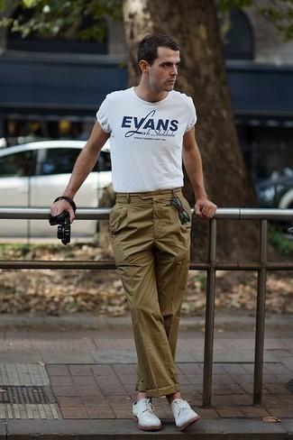 Tenue: T-shirt à col rond imprimé blanc et bleu marine, Pantalon chino olive, Chaussures derby en daim blanches, Lunettes de soleil vert foncé