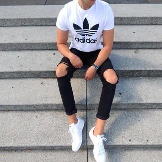 Comment porter: t-shirt à col rond imprimé blanc et noir, jean skinny déchiré noir, baskets basses en cuir blanches, montre en cuir noire