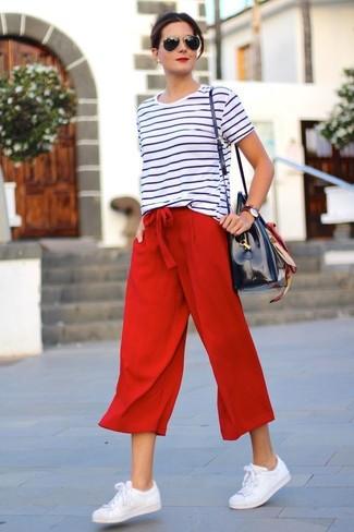 Comment porter: t-shirt à col rond à rayures horizontales blanc et noir, jupe-culotte rouge, baskets basses en cuir blanches, sac fourre-tout en cuir bleu marine