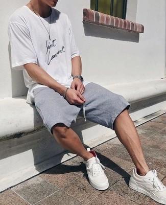 Comment s'habiller à 20 ans: Harmonise un t-shirt à col rond imprimé blanc et noir avec un short de running gris pour un look confortable et décontracté. Complète cet ensemble avec une paire de des baskets basses en cuir blanches pour afficher ton expertise vestimentaire.