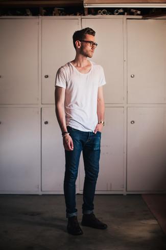 Comment porter: t-shirt à col rond blanc, jean skinny bleu marine, bottines chukka en cuir marron foncé, montre dorée