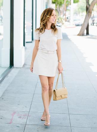 Comment porter: t-shirt à col rond blanc, minijupe blanche, sandales à talons en cuir beiges, cartable en cuir matelassé marron clair