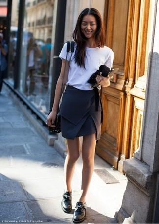Comment porter: t-shirt à col rond blanc, minijupe noire, slippers en cuir noirs, sac bandoulière en cuir noir