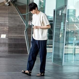Comment s'habiller à l'adolescence: Associe un t-shirt à col rond blanc avec un pantalon chino bleu marine pour affronter sans effort les défis que la journée te réserve. Tu veux y aller doucement avec les chaussures? Fais d'une paire de sandales en toile noires ton choix de souliers pour la journée.