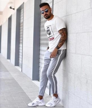Comment porter: t-shirt à col rond imprimé blanc, pantalon chino gris, chaussures de sport blanches, lunettes de soleil bleu marine