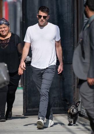 Comment porter: t-shirt à col rond blanc, pantalon chino gris foncé, baskets basses en cuir blanches, lunettes de soleil marron foncé