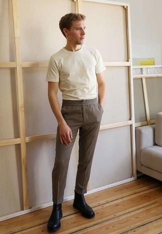 Comment porter des bottines chelsea en cuir noires: Marie un t-shirt à col rond blanc avec un pantalon chino marron pour une tenue confortable aussi composée avec goût. Une paire de des bottines chelsea en cuir noires apportera une esthétique classique à l'ensemble.