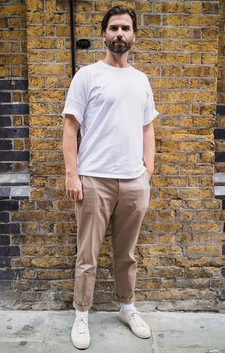 Comment porter un pantalon chino marron clair: Associe un t-shirt à col rond blanc avec un pantalon chino marron clair pour affronter sans effort les défis que la journée te réserve. Une paire de des baskets basses en toile blanches est une option génial pour complèter cette tenue.