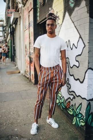Comment porter un pantalon chino tabac: Pour une tenue de tous les jours pleine de caractère et de personnalité harmonise un t-shirt à col rond blanc avec un pantalon chino tabac. Cet ensemble est parfait avec une paire de des baskets basses en cuir blanches et noires.