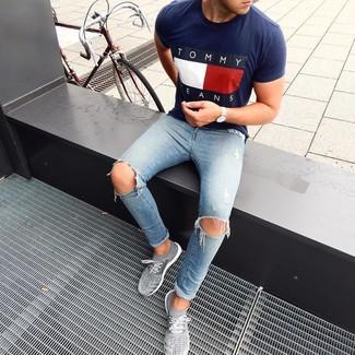 Comment porter: t-shirt à col rond imprimé bleu marine, jean skinny déchiré bleu clair, chaussures de sport grises, montre argentée