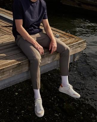 Comment porter un pantalon chino beige: Pour créer une tenue idéale pour un déjeuner entre amis le week-end, pense à opter pour un t-shirt à col rond bleu marine et un pantalon chino beige. Une paire de des baskets basses en cuir blanches est une option astucieux pour complèter cette tenue.