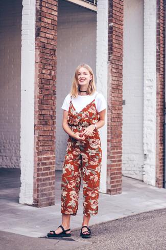 Comment porter: t-shirt à col rond blanc, combinaison pantalon à fleurs rouge, sandales plates en cuir noires, collier ras de cou noir