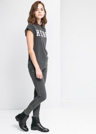 Comment porter: t-shirt à col rond imprimé gris foncé, jean skinny gris foncé, bottines chelsea en cuir noires, chaussettes en laine gris foncé