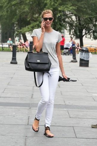Comment porter: t-shirt à col rond gris, jean skinny blanc, sandales plates en cuir noires, cartable en cuir noir