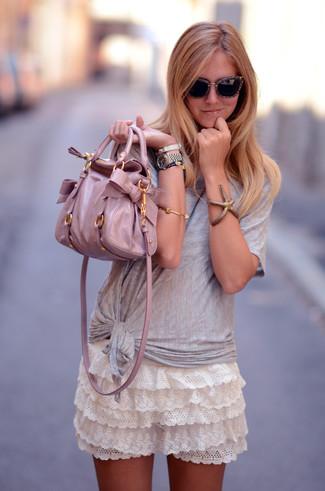 Comment porter une minijupe à volants blanche: Un t-shirt à col rond gris et une minijupe à volants blanche sont ta tenue incontournable pour les jours de détente.