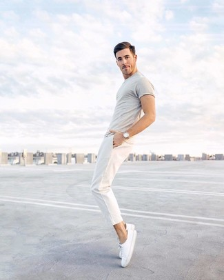 Comment porter: t-shirt à col rond gris, pantalon chino blanc, baskets basses en toile blanches, montre en cuir marron clair