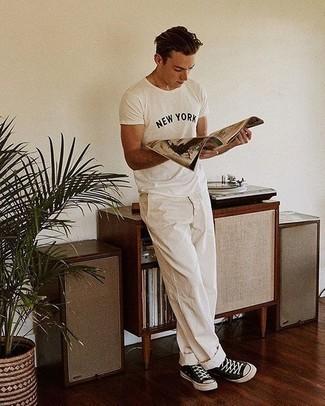 Comment porter des baskets basses en toile noires et blanches: Harmonise un t-shirt à col rond imprimé blanc et noir avec un pantalon chino blanc pour une tenue idéale le week-end. Une paire de des baskets basses en toile noires et blanches s'intégrera de manière fluide à une grande variété de tenues.