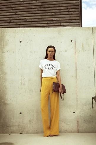 Comment porter: t-shirt à col rond imprimé blanc et noir, pantalon large jaune, sac bandoulière en cuir marron