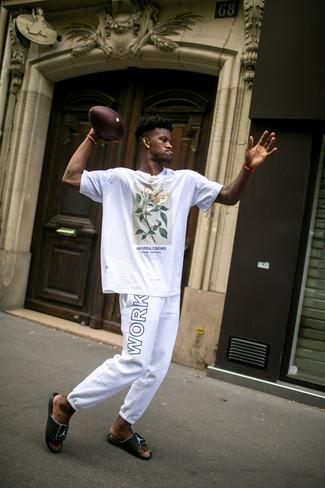 Comment porter: t-shirt à col rond imprimé blanc, pantalon de jogging imprimé blanc et noir, sandales en caoutchouc noires