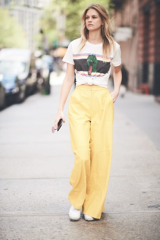Comment porter: t-shirt à col rond imprimé blanc, pantalon large jaune, baskets basses en toile blanches