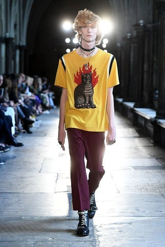 Comment porter: t-shirt à col rond imprimé jaune, pantalon chino pourpre, bottes de loisirs en cuir noires