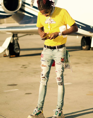 Comment porter: t-shirt à col rond imprimé jaune, jean skinny déchiré bleu clair, chaussures de sport marron clair, ceinture en cuir tressée noire