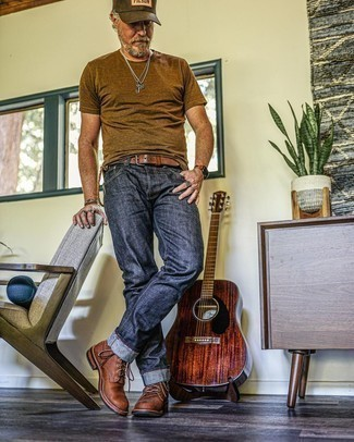 Comment s'habiller après 50 ans: Pour une tenue de tous les jours pleine de caractère et de personnalité choisis un t-shirt à col rond marron et un jean bleu marine. Fais d'une paire de bottes de loisirs en cuir marron ton choix de souliers pour afficher ton expertise vestimentaire.