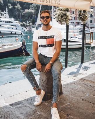Comment porter: t-shirt à col rond imprimé blanc, jean skinny déchiré bleu, baskets basses en cuir blanches, lunettes de soleil noires