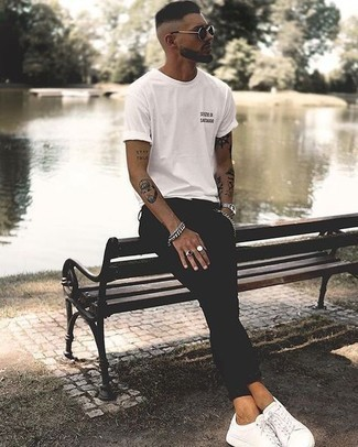 Comment porter un t-shirt à col rond: Pense à porter un t-shirt à col rond et un jean skinny noir pour un look confortable et décontracté. Rehausse cet ensemble avec une paire de des baskets basses en toile blanches.