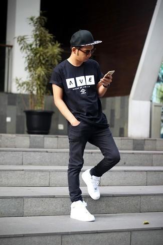 Tendances mode hommes: Pense à opter pour un t-shirt à col rond imprimé noir et blanc et un jean skinny noir pour un look idéal le week-end. Jouez la carte classique pour les chaussures et fais d'une paire de baskets basses en cuir blanches ton choix de souliers.