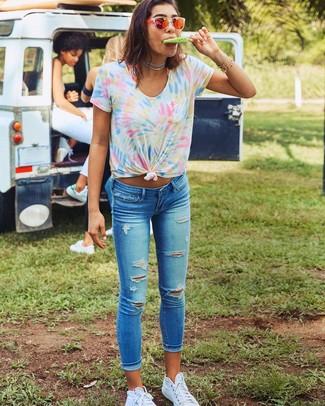 Comment porter: t-shirt à col rond imprimé tie-dye multicolore, jean skinny déchiré bleu, baskets montantes en toile blanches, lunettes de soleil orange