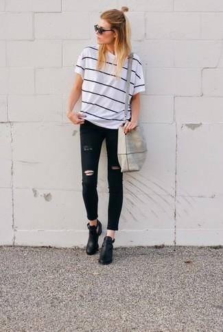 Comment porter: t-shirt à col rond à rayures horizontales blanc et noir, jean skinny déchiré noir, bottines en cuir découpées noires, sac fourre-tout en toile gris