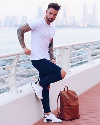 Comment porter: t-shirt à col rond blanc, jean skinny déchiré bleu marine, chaussures de sport blanches, sac à dos en cuir tabac
