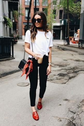 Comment porter: t-shirt à col rond blanc, jean skinny noir, slippers en cuir rouges, sac bandoulière en cuir matelassé noir