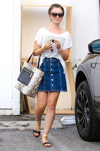 Comment porter: t-shirt à col rond imprimé blanc et bleu, jupe boutonnée en denim bleue, sandales plates en cuir noires, sac fourre-tout en cuir imprimé serpent gris