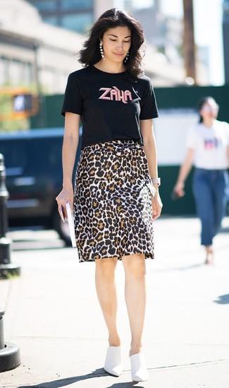 Comment porter: t-shirt à col rond imprimé noir, jupe crayon imprimée léopard marron, mules en cuir blanches, montre en cuir blanche