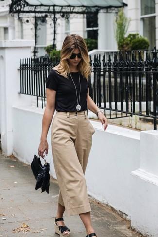 Comment porter: t-shirt à col rond noir, jupe-culotte beige, sandales compensées en cuir noires, pochette en cuir noire