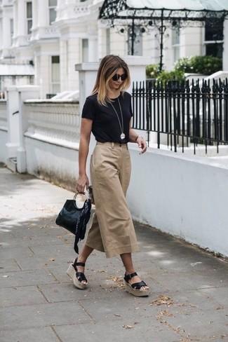 Comment porter: t-shirt à col rond noir, jupe-culotte marron clair, sandales compensées en cuir noires, pochette en cuir noire