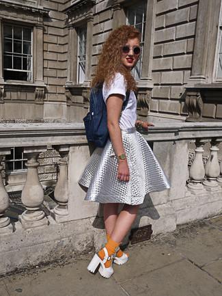 Comment porter: t-shirt à col rond blanc, jupe évasée argentée, sandales à talons en cuir épaisses blanches, sac à dos en denim bleu marine