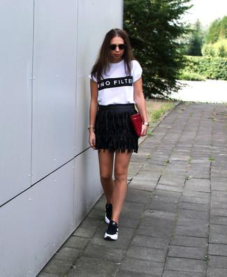 Comment porter: t-shirt à col rond imprimé blanc et noir, minijupe en cuir à franges noire, chaussures de sport noires et blanches, pochette en cuir bordeaux