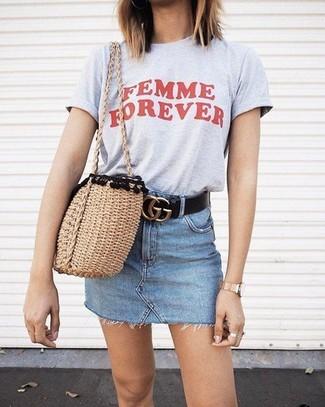 Comment porter: t-shirt à col rond imprimé gris, minijupe en denim bleu clair, sac fourre-tout de paille marron clair, ceinture en cuir noire