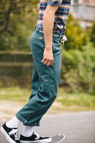 Tendances mode hommes: Pour une tenue de tous les jours pleine de caractère et de personnalité essaie de marier un t-shirt à col rond à rayures horizontales multicolore avec un pantalon chino bleu canard. Une paire de des baskets basses en toile noires et blanches est une option judicieux pour complèter cette tenue.