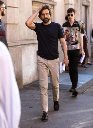 Comment porter un pantalon chino marron clair: Harmonise un t-shirt à col rond noir avec un pantalon chino marron clair pour une tenue idéale le week-end. Apportez une touche d'élégance à votre tenue avec une paire de des slippers en cuir noirs.