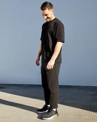 Tendances mode hommes: Associe un t-shirt à col rond noir avec un pantalon chino noir pour obtenir un look relax mais stylé. Si tu veux éviter un look trop formel, opte pour une paire de chaussures de sport noires et blanches.