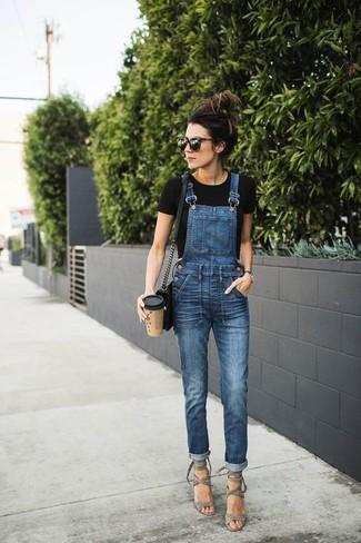 Comment porter: t-shirt à col rond noir, salopette en denim bleue, sandales à talons en daim grises, sac bandoulière en cuir noir