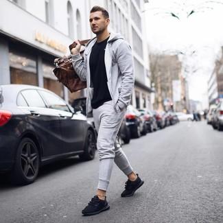Comment porter: t-shirt à col rond noir, survêtement gris, chaussures de sport noires, fourre-tout en cuir marron