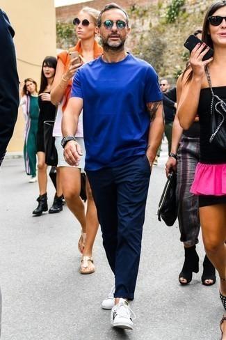 Tendances mode hommes: Marie un t-shirt à col rond bleu avec un pantalon chino bleu marine pour une tenue confortable aussi composée avec goût. Cet ensemble est parfait avec une paire de des baskets basses en cuir blanches.